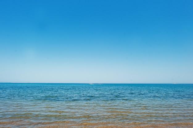 地平線上の青い海でボートを実行
