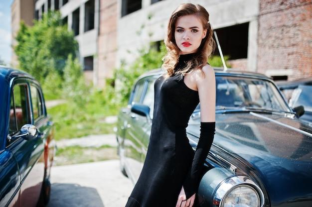 Портрет красивой фотомодели с ярким макияжем в стиле ретро оперся на старинный автомобиль