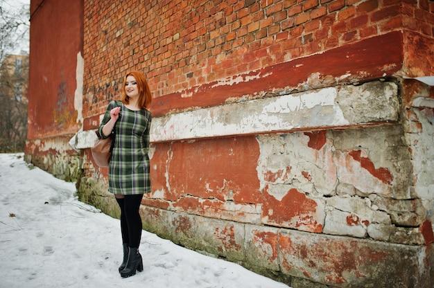 冬の日にレンガの壁に立っている女性のバックパックと市松模様のドレスを着ている赤い髪の若いきれいな女性の屋外のポートレート。