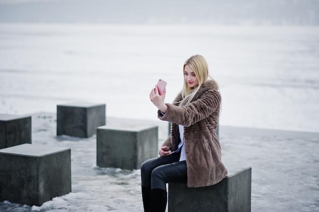 冬の日に凍った湖に対して石キューブを手にピンクのスマートフォンで探している毛皮のコートでスタイリッシュな豊かな若いブロンドの女性。