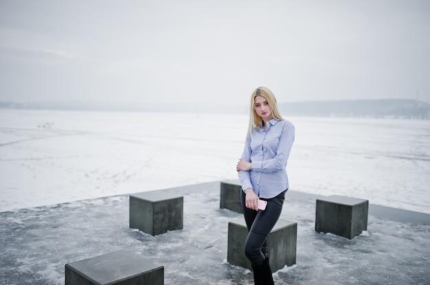 スタイリッシュな金持ちの若いブロンドの女性のブラウスと革のズボンに手にピンクのスマートフォン、冬の日に凍った湖に対して石キューブ。