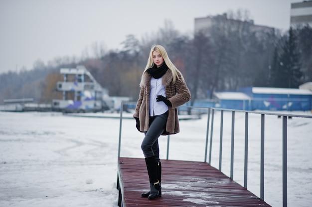 Портрет молодой женщины блондинки элегантности в шубе на пирсе, туманной реке на зимнем льду.