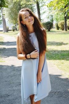 夏の公園の緑に対して青いブラウスで美しい十代の少女の肖像画は彼女の髪で遊ぶ。
