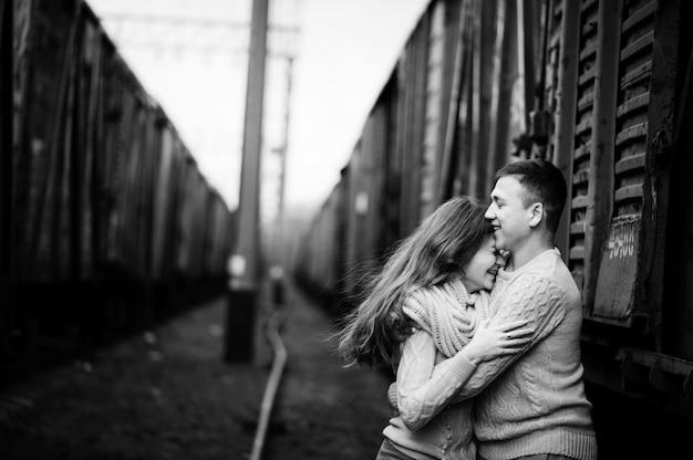 Молодая пара в теплых свитерах, обнимающих друг друга на железнодорожных станциях