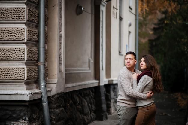 秋の都市でアーチの下で愛を抱いて結ばれた暖かいセーターを着た若いカップル。