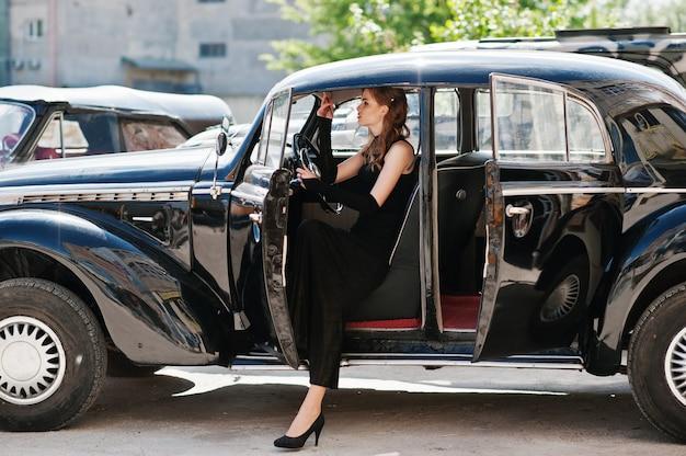 手にタバコを持つヴィンテージ車に座っているレトロなスタイルの明るいメイクと美しいセクシーなファッションの女の子モデルの肖像画。