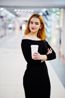 貿易ショッピングセンターでコーヒーカップを保持している明るいメイクと黒のドレスにファッションの赤い髪の少女服