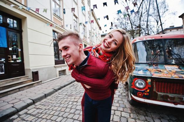 背景の古いレトロなビンテージバスを楽しんで、旧市街での愛の物語の赤いドレスの若い美しいスタイリッシュなファッションカップル