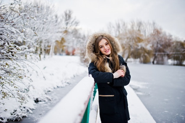 冬の暖かい服装で美しいブルネットの少女。公園で凍った湖に対する冬のジャケットのモデル。
