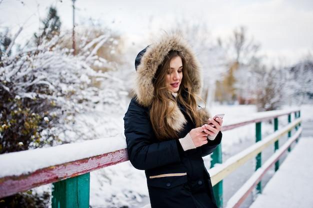冬の暖かい服装で美しいブルネットの少女。公園で凍った湖に対する冬のジャケットのモデルは、携帯電話で話します。