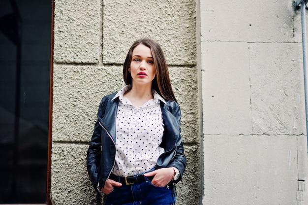 Портрет стильной молодой женщины в кожаной куртке и рваных джинсах на улицах города