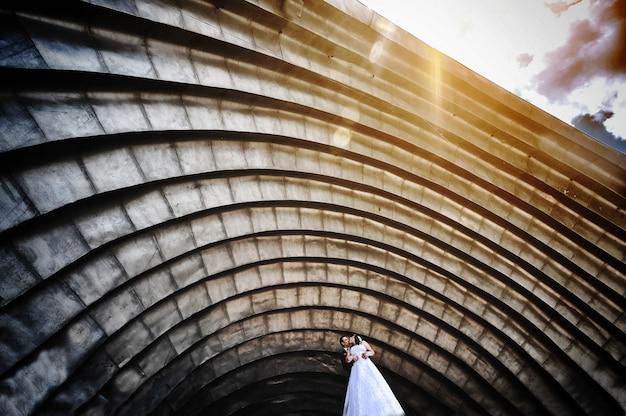 日没の大きなアリーナホールアーチの下で結婚式のカップル
