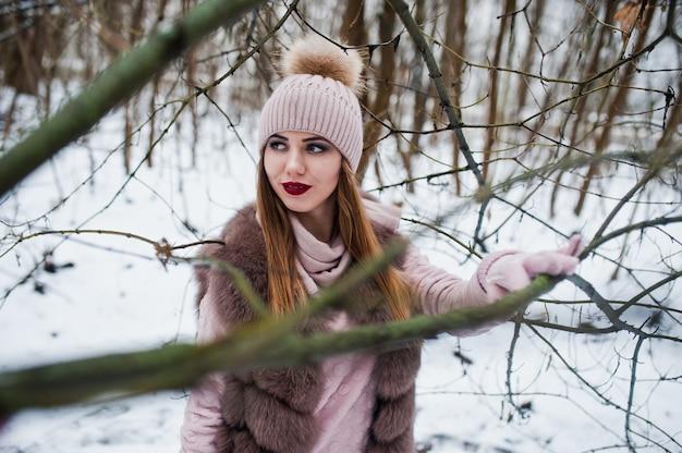 毛皮のコートと冬の森で帽子のスタイリッシュな女性。