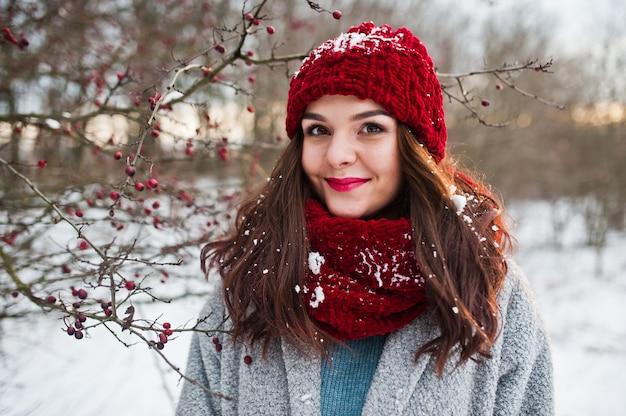 雪に覆われた木の枝の近くの灰色のコート、赤い帽子、スカーフで穏やかな少女の肖像画。