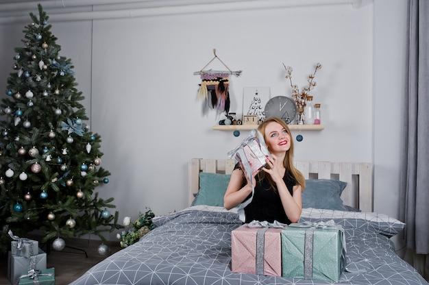 Милая белокурая девушка на черном платье лежа на кровати с коробками подарков против рождественской елки.