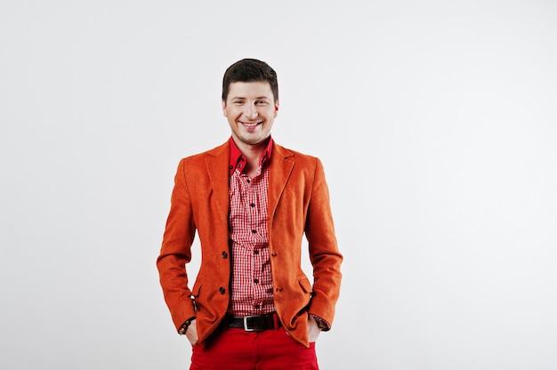 Фасонируйте смеющегося молодого человека в оранжевом костюме и красных брюках