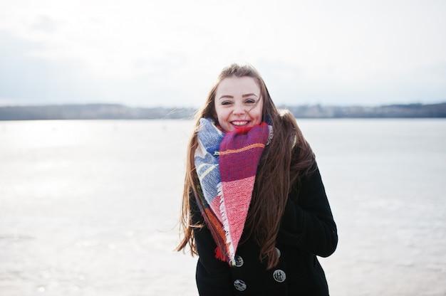 Случайные молодая девушка в черном пальто и шарф против замерзшей реки на солнечную зимнюю погоду.