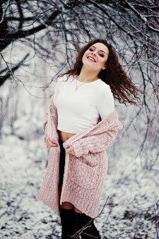 雪の風景に巻き毛のブルネットの少女