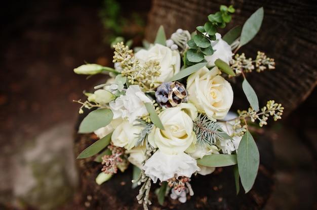 Фото конца-вверх букета свадьбы сделанного из белых роз и других трав кладя на деревянную поверхность.