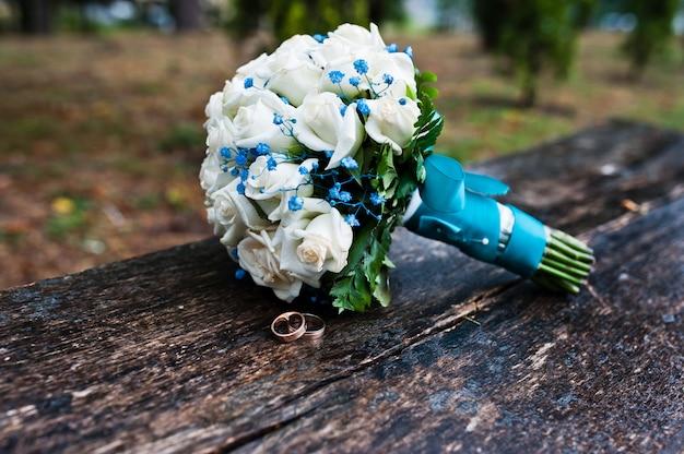 木製のベンチに白いバラとターコイズブルーのリボンでウェディングブーケ
