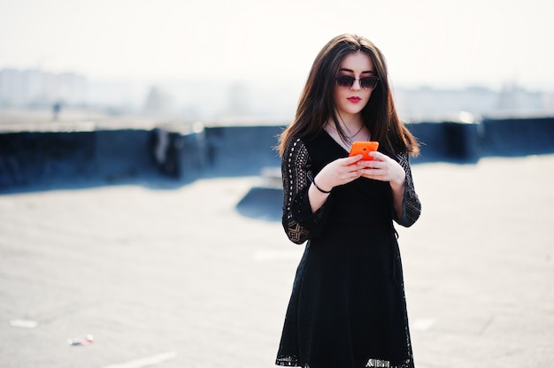 赤い唇と手でオレンジ色の携帯電話を持つブルネットの少女の肖像画、黒いドレスを着て、屋根にポーズのサングラス