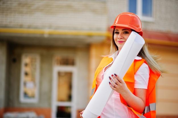 Инженер строитель женщина в форме жилет и оранжевый защитный шлем держать деловую бумагу против нового здания