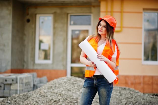 均一なチョッキとオレンジ色の保護ヘルメットのエンジニアビルダーの女性は、新しい建物に対してビジネス描画紙ロールを保持します。