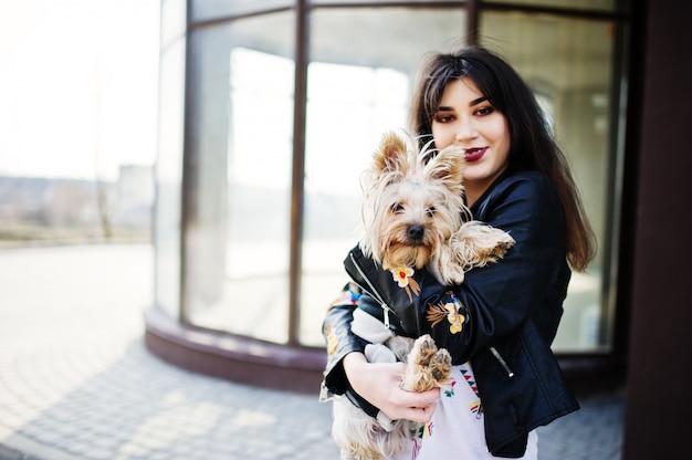 Цыганка брюнетки с собакой йоркширского терьера позировала против большого дома окон. модельное ношение на кожаной куртке с орнаментом, брюки