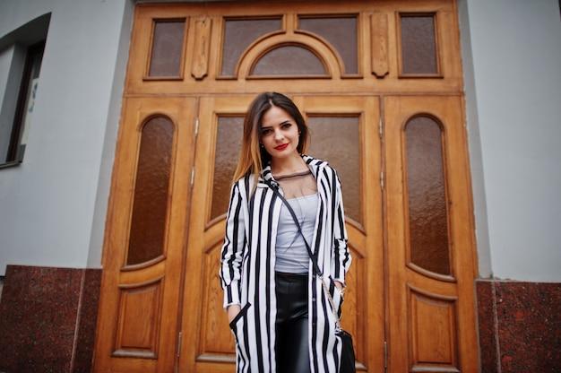 ファッショナブルな女性は黒と白のストライプスーツジャケット、革のズボン、建物の大きな木製のドアに対してポーズで見てください。ファッションの女の子の概念。