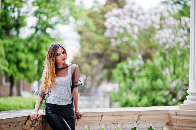 おしゃれな女性は、白いシャツ、黒い透明な服、革のズボン、通りでポーズを見てください。ファッションの女の子の概念。