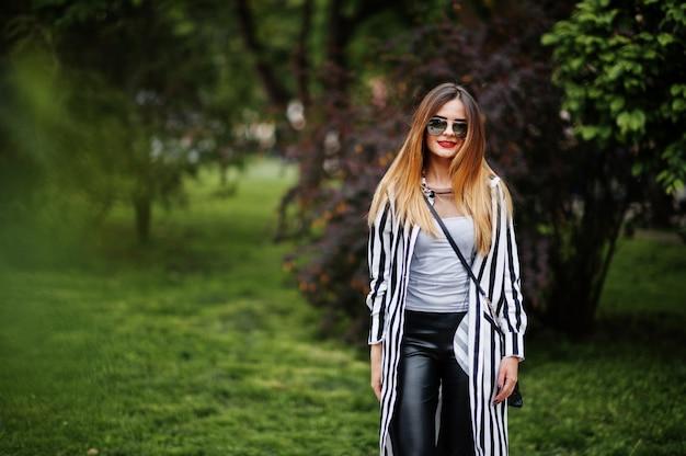 ファッショナブルな女性は、黒と白のストライプスーツジャケット、革のズボン、サングラスの通りで茂みに対してポーズで見てください。ファッションの女の子の概念。
