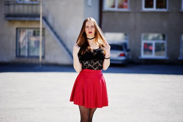 彼女の首に黒いチョーカーネックレスと街の通りで赤い革のスカートを持つ少女の肖像画。