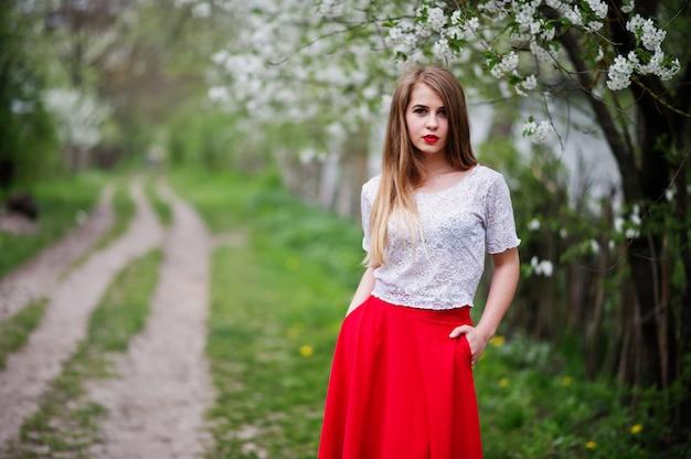 Портрет красивой девушки с красными губами в весеннем цвету саду, носить красное платье и белая блузка.