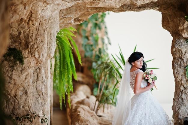洞窟の装飾でポーズをとって刺激的なウェディングドレスで誘惑モデルブルネット花嫁