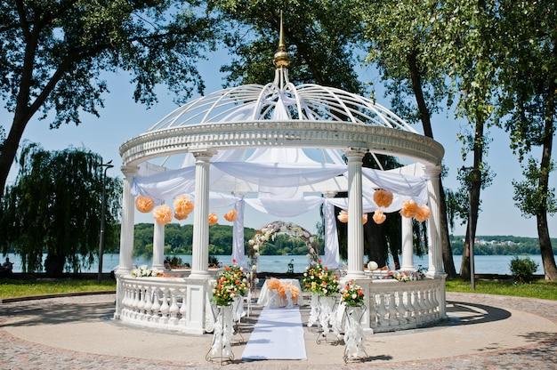 椅子と多くの花と装飾が施された結婚式のアーチ