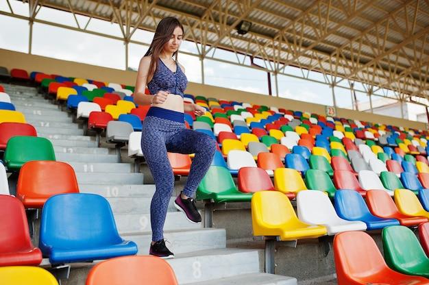 スタジアムの階段を駆け上がるアクティブな若い女性。