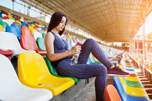 Портрет милой женщины в усаживании спортивной одежды и питьевой воде в стадионе.