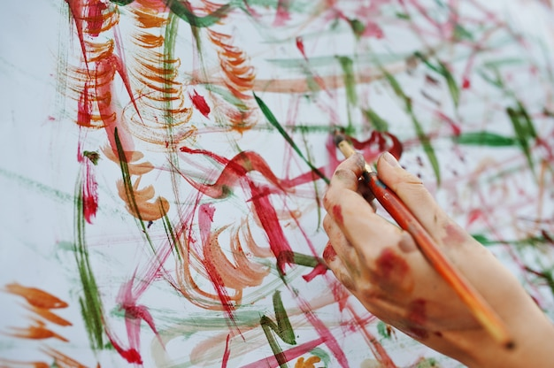 水彩絵の具で紙に女性の手の絵のクローズアップ写真。