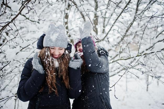 Две веселые подруги, весело в снежный зимний день возле заснеженных деревьев.