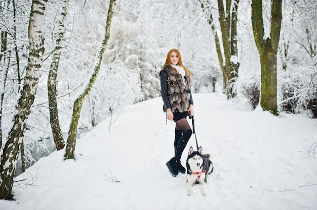 Красная с волосами девушка гуляя на парк с осиплой собакой на зимний день.