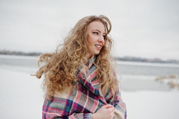 Кудрявая блондинка девушка в клетчатой плед против замерзшего озера в зимний день.