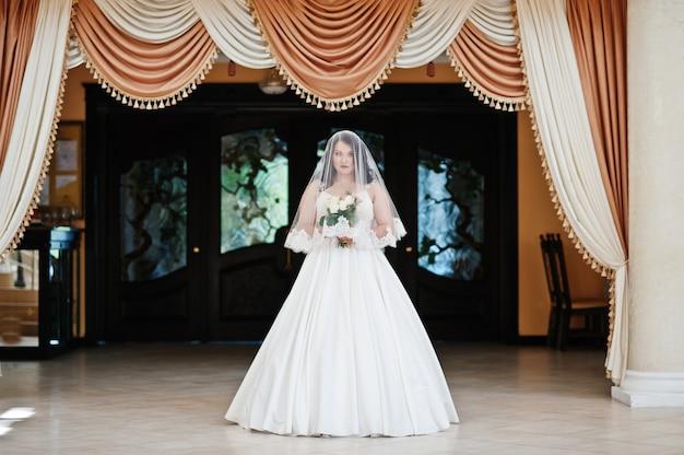 結婚式場でベールの下でポーズをとって結婚式ブーケと巨乳ブルネットの花嫁