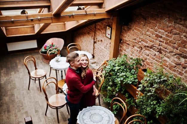 屋根の大きな窓とビンテージカフェで愛の物語の赤いドレスを着た若い美しいスタイリッシュなカップル