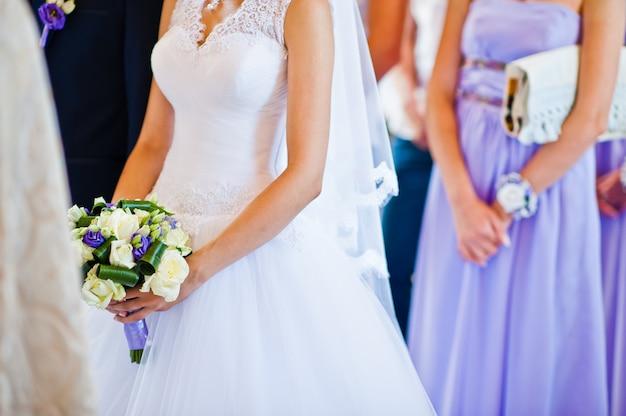 花嫁の背景新郎と新婦付け添人の手に紫のウェディングブーケ