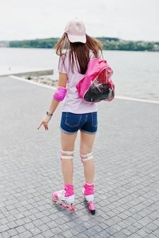 公園の舗装でローラーブレードをカジュアルな服装で格好良い若い女性の肖像画。