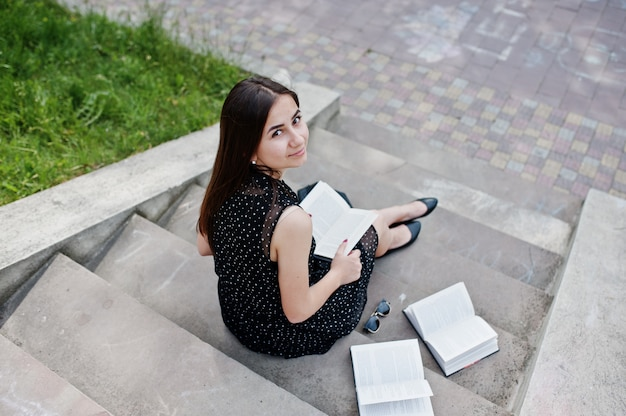 階段に座って、公園で読書黒の水玉ドレスの素晴らしい女性の肖像画。