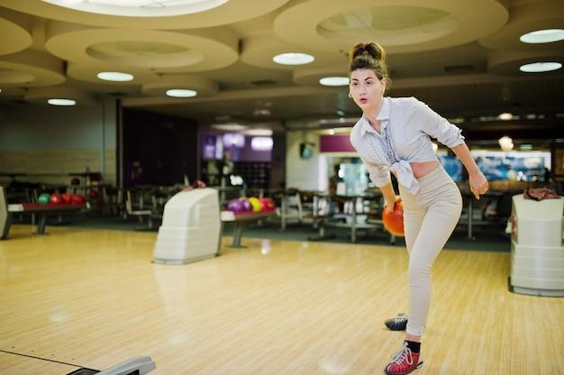 Девушка с боулинг мяч на аллее играл в боулинг-клубе.