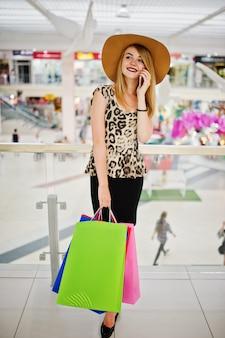 Портрет женщины в леопардовой блузке, черной юбке, идущей в торговом центре с сумками и говорящей по телефону.
