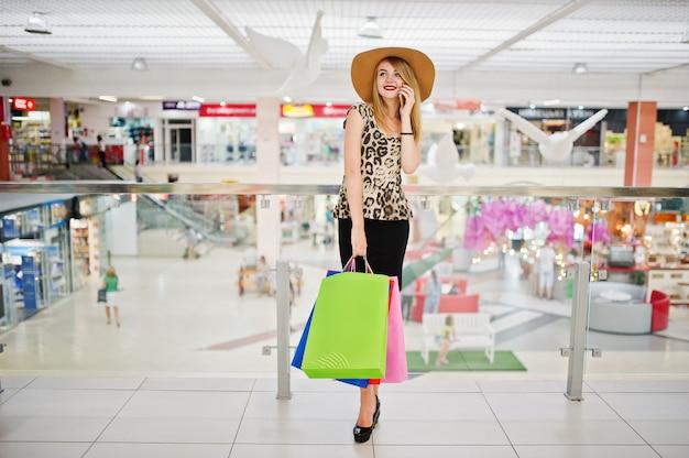 バッグとショッピングモールを歩いて、電話で話しているヒョウブラウス、黒スカートの女性の肖像画。