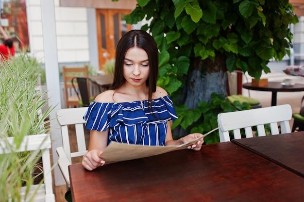 Великолепная брюнетка женщина сидит на столе в кафе и глядя на меню.
